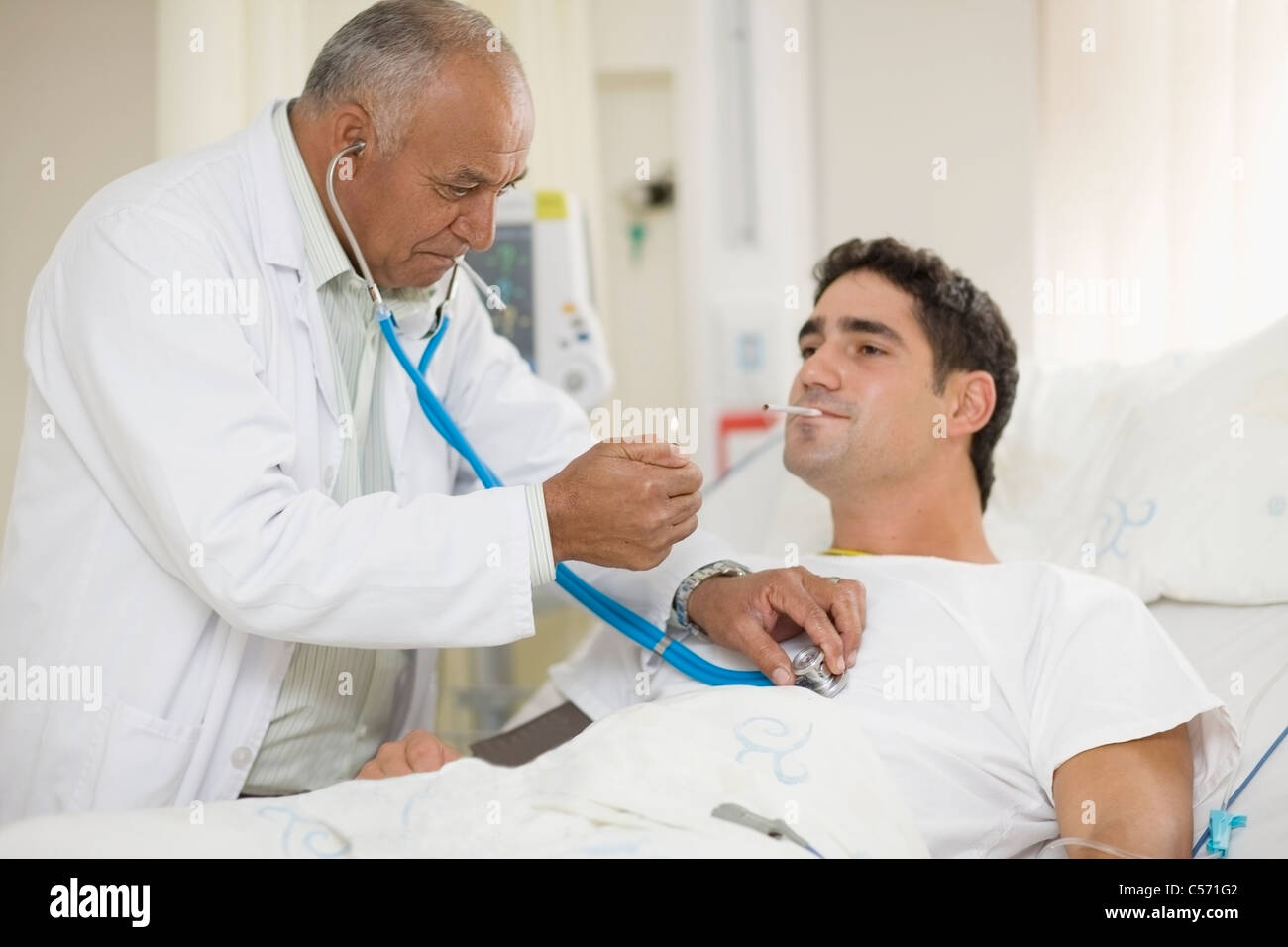 Doctor lighting patient's cigarette - Stock Image