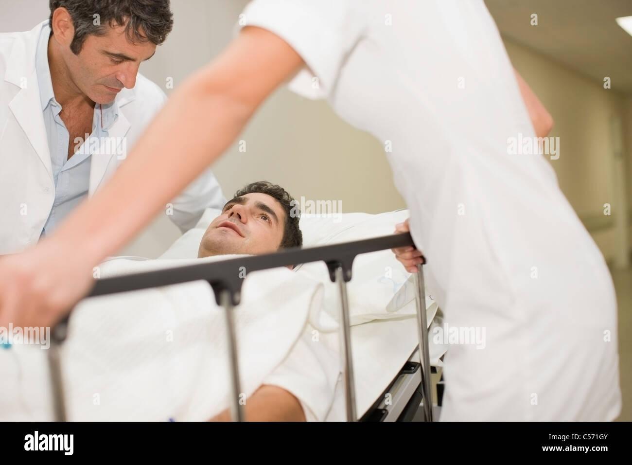 Doctors rushing patient down hallway - Stock Image