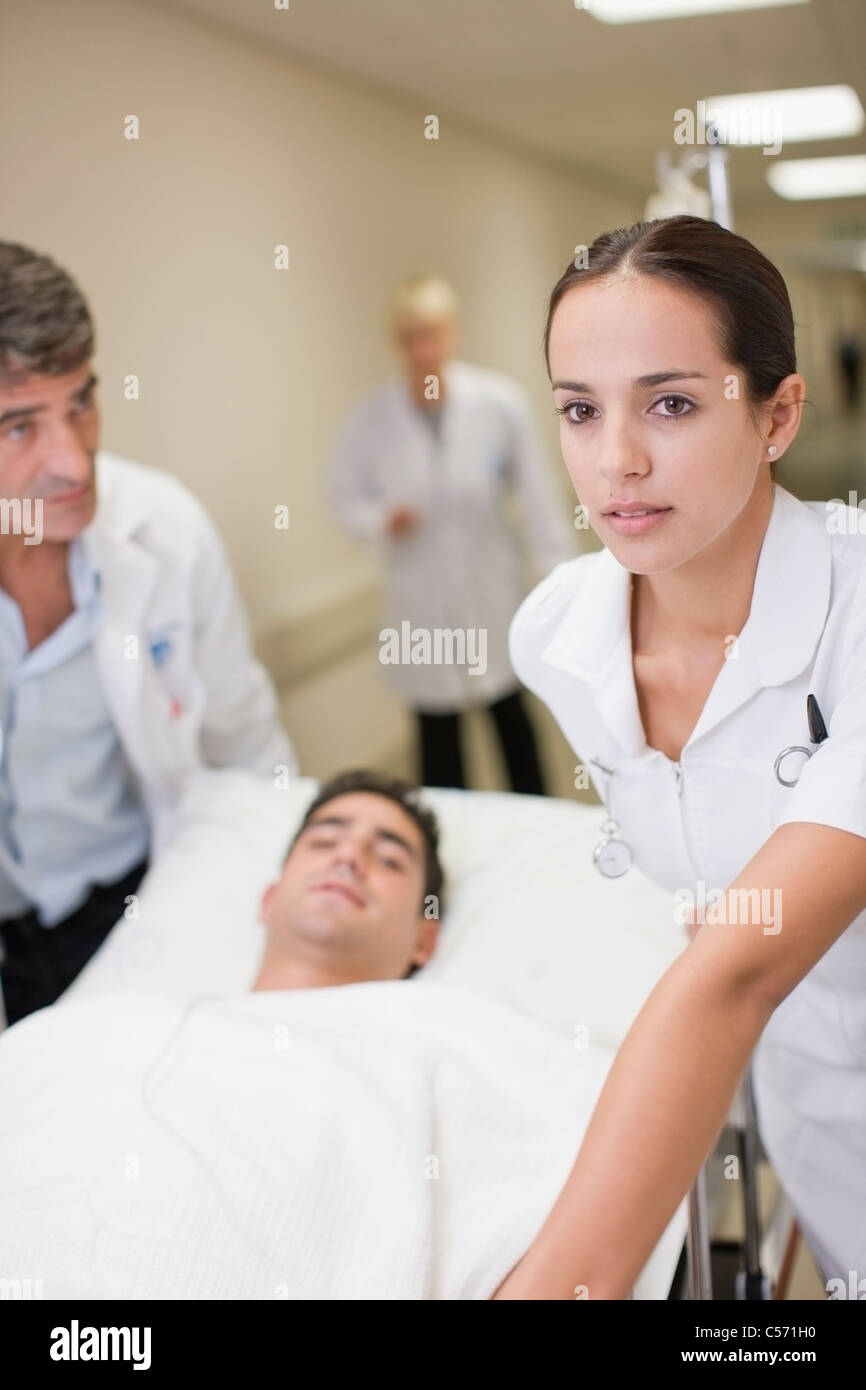 Nurse rushing patient down hallway - Stock Image
