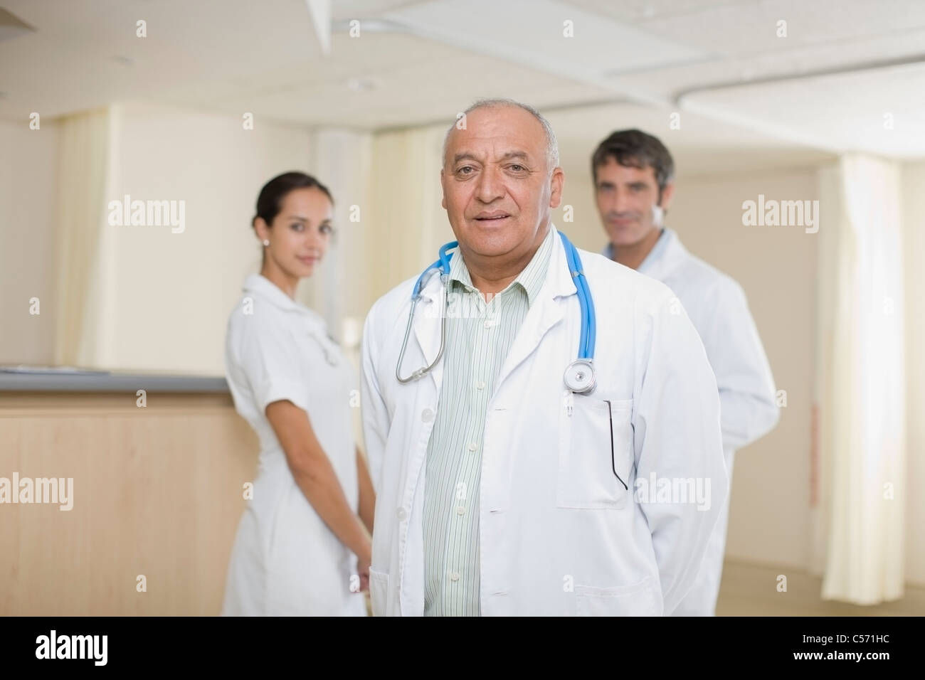 Doctors and nurse standing in hospital - Stock Image