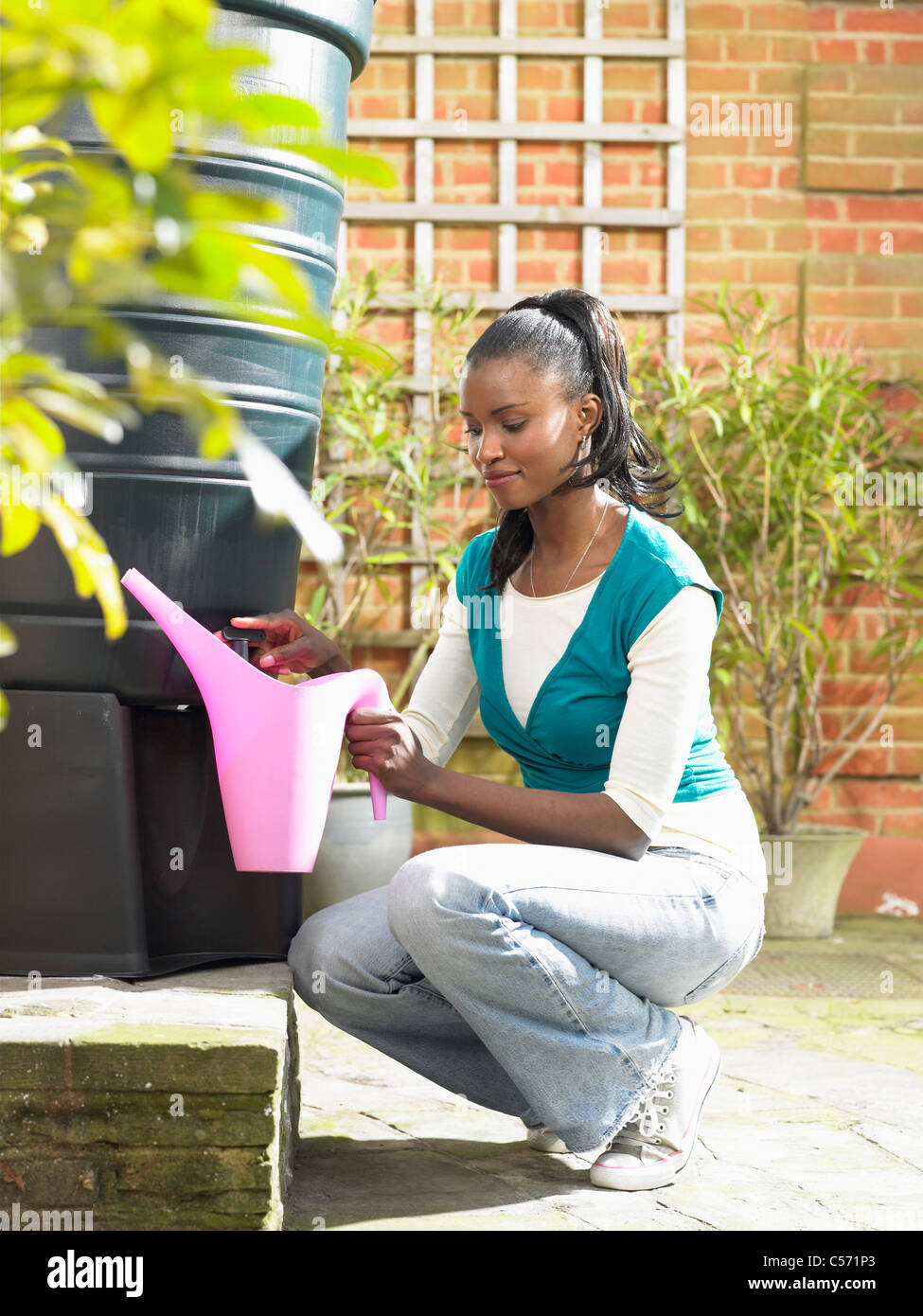 Woman filling jug with recycled water - Stock Image