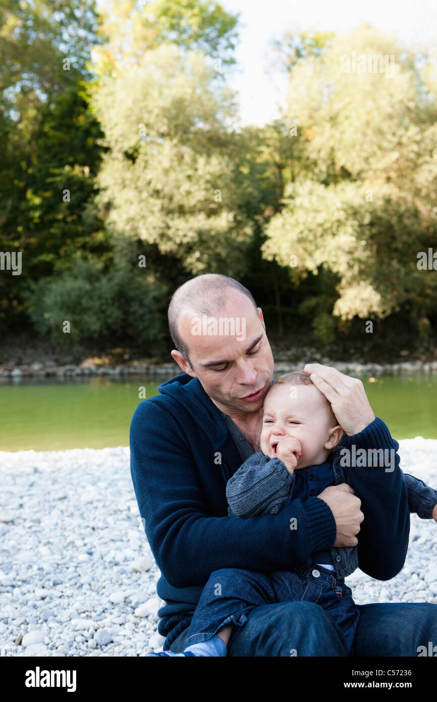Father holding crying baby by creek - Stock Image