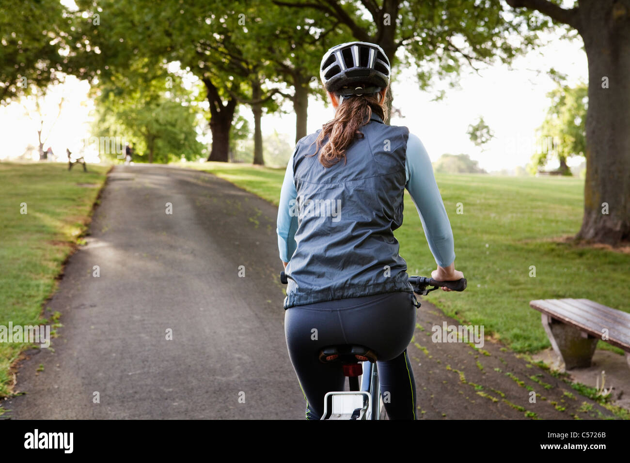Woman cycling uphill at park - Stock Image