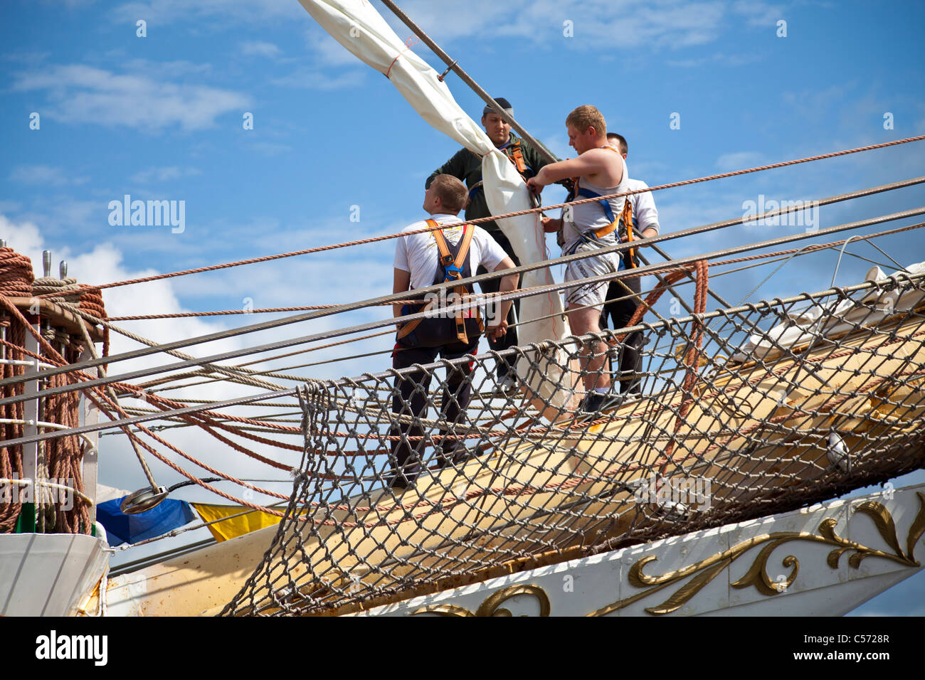 Men standing of the bowsprit of the Dar Mlodziezy, working on the rigging of a sail. Greenock, Scotland, UK - Stock Image
