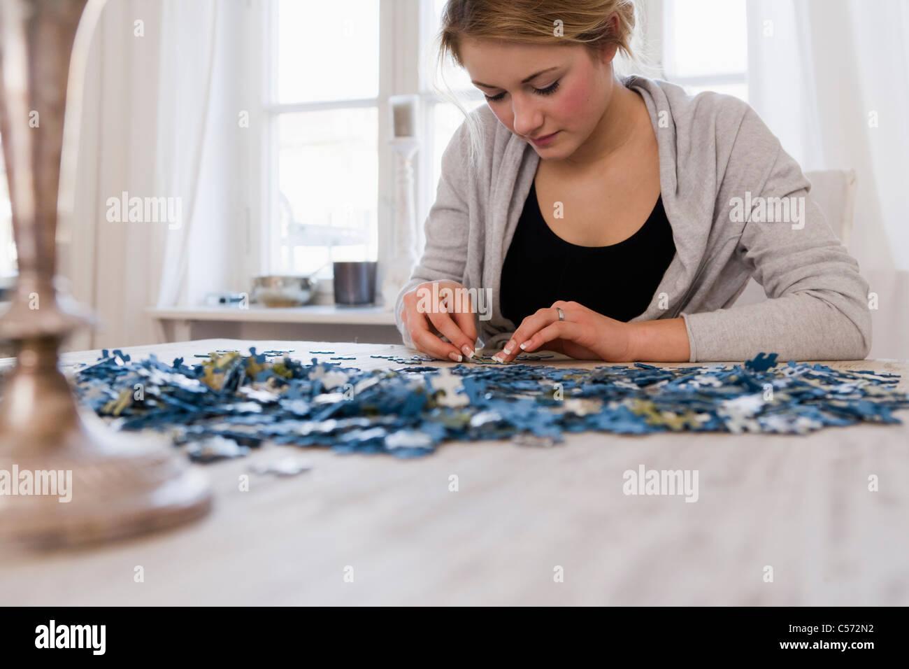 Teenage girl working on jigsaw puzzle - Stock Image