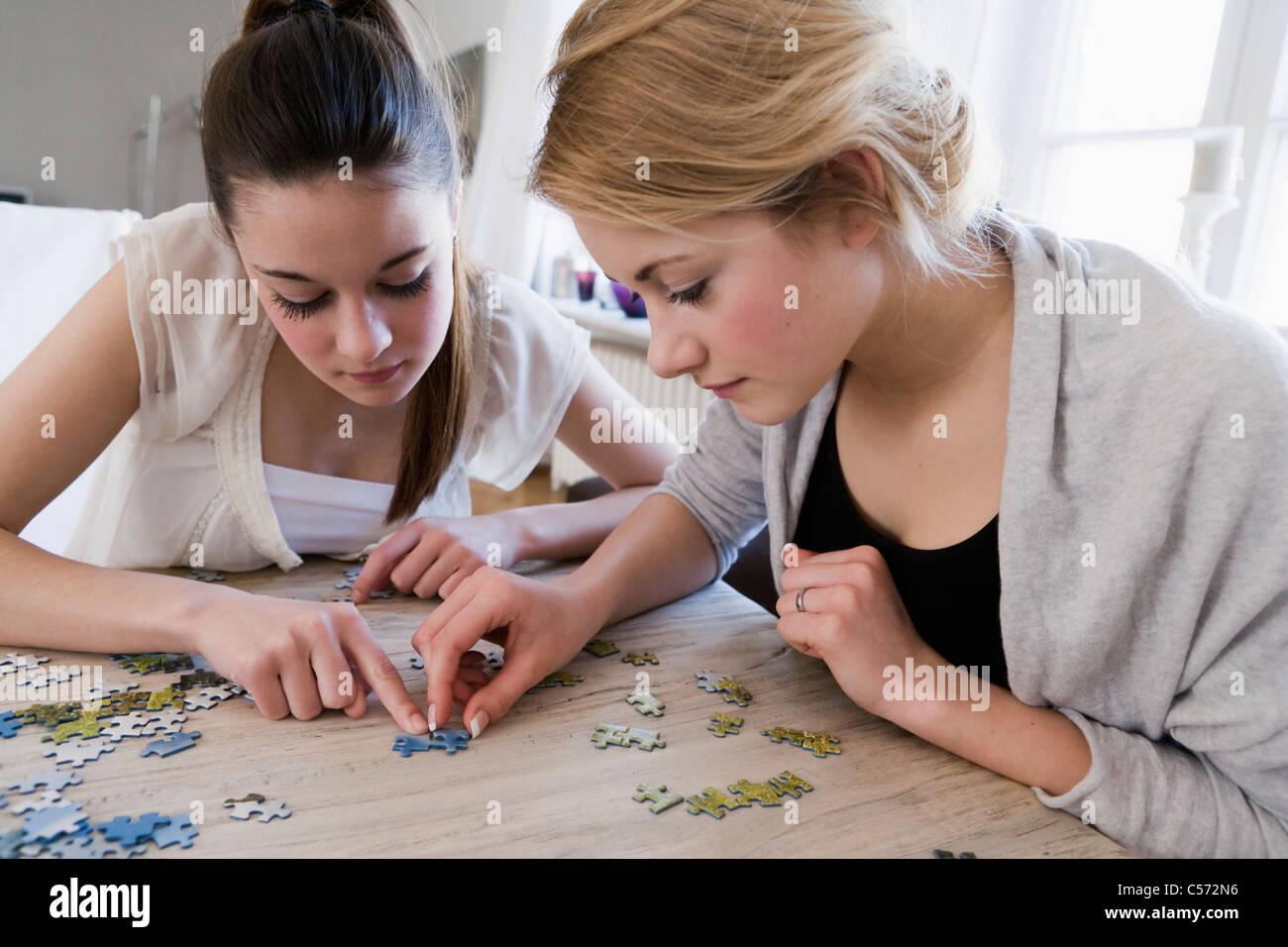 Teenage girls working on jigsaw puzzle - Stock Image