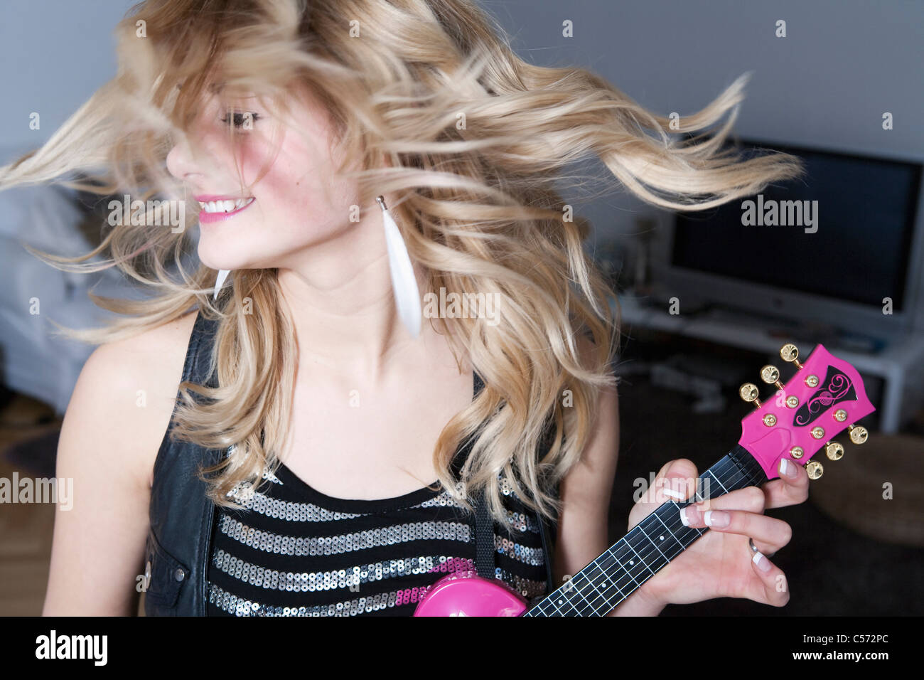 Teenage girl holding miniature guitar - Stock Image