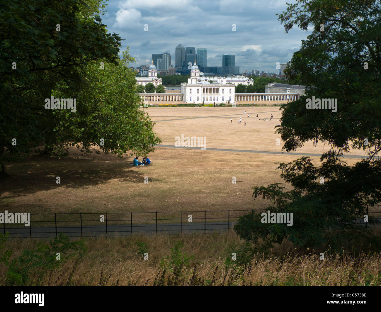 View across very dry Greenwich Park towards the National Maritime Museum in Greenwich, London, with Docklands in - Stock Image