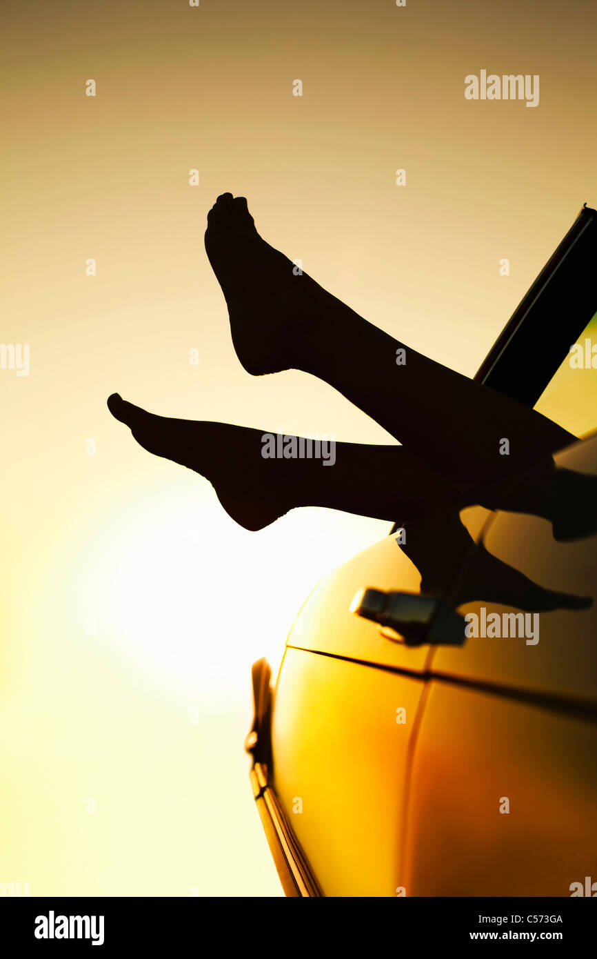 Woman's feet sticking out of car window - Stock Image