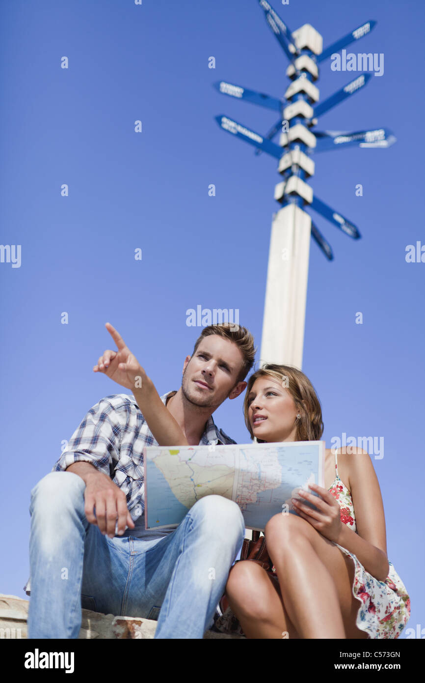 Couple reading map at crossroads - Stock Image