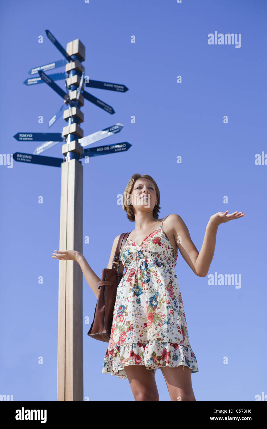 Confused woman at crossroads - Stock Image