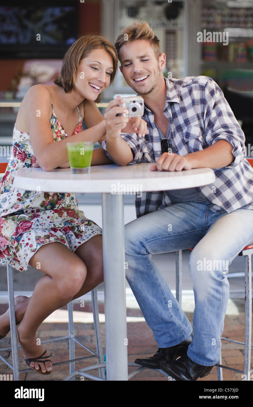 Couple admiring photos at cafe - Stock Image