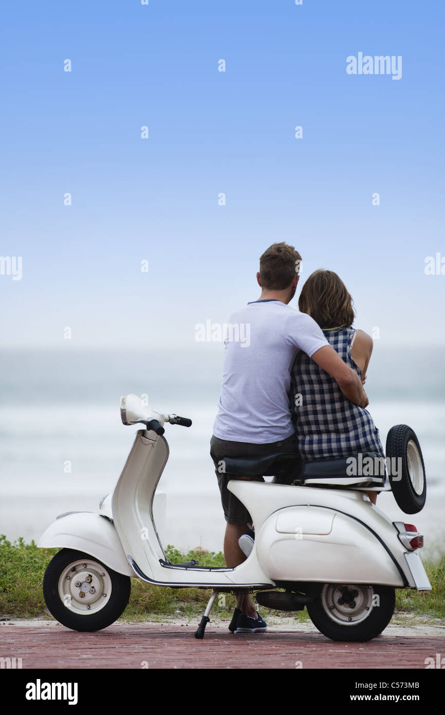 Couple sitting on scooter together - Stock Image