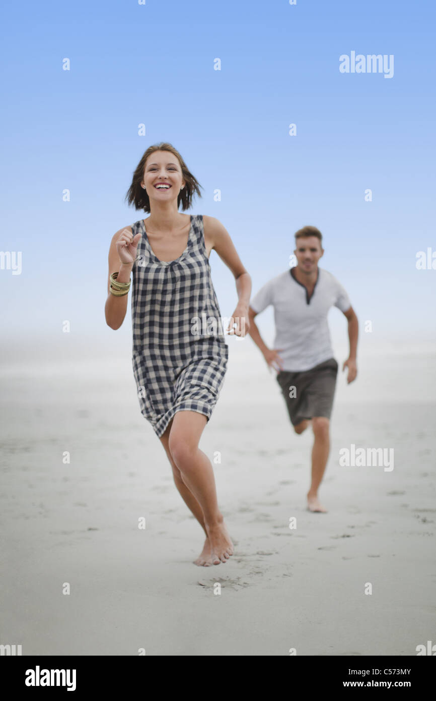 Couple chasing each other on beach - Stock Image