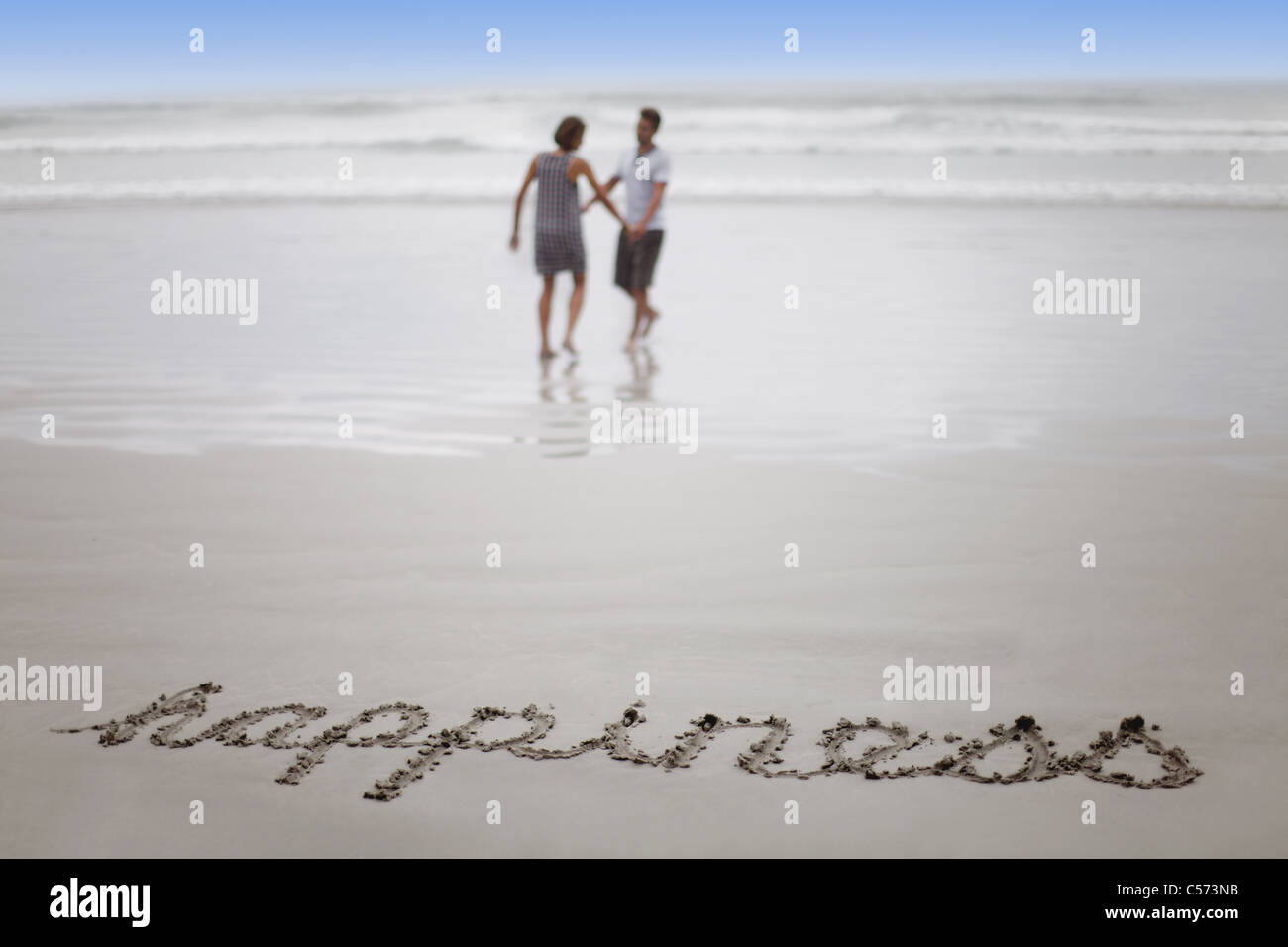 'Happiness' in sand with couple on beach - Stock Image