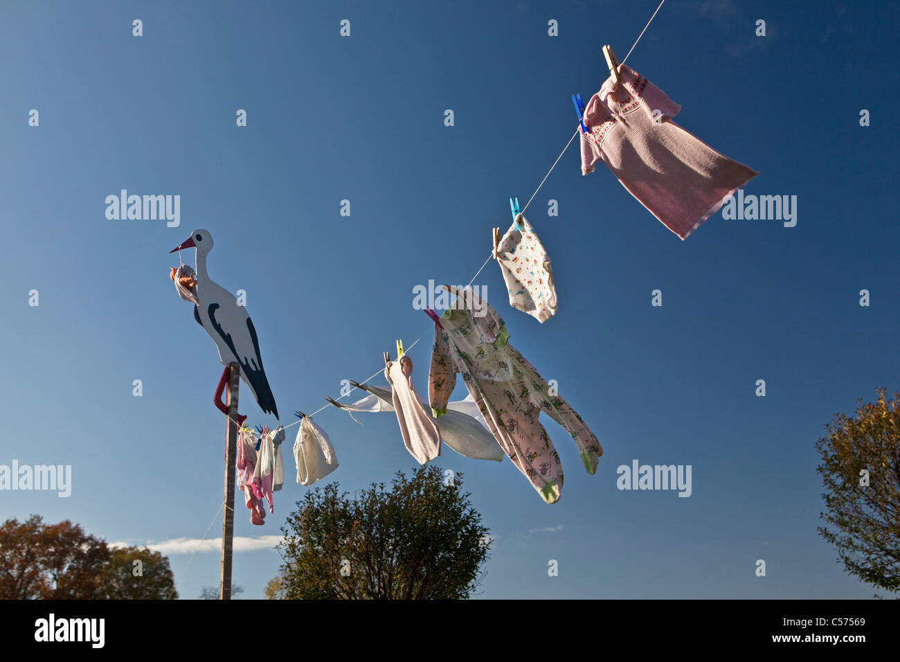 The Netherlands, Lattrop, Wooden stork with baby doll, to show that a baby has born. Baby clothes on clothesline. - Stock Image
