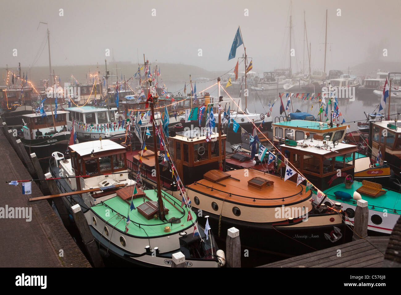 The Netherlands, Vollenhoven, Gathering of former towboats in harbour. Morning mist. - Stock Image