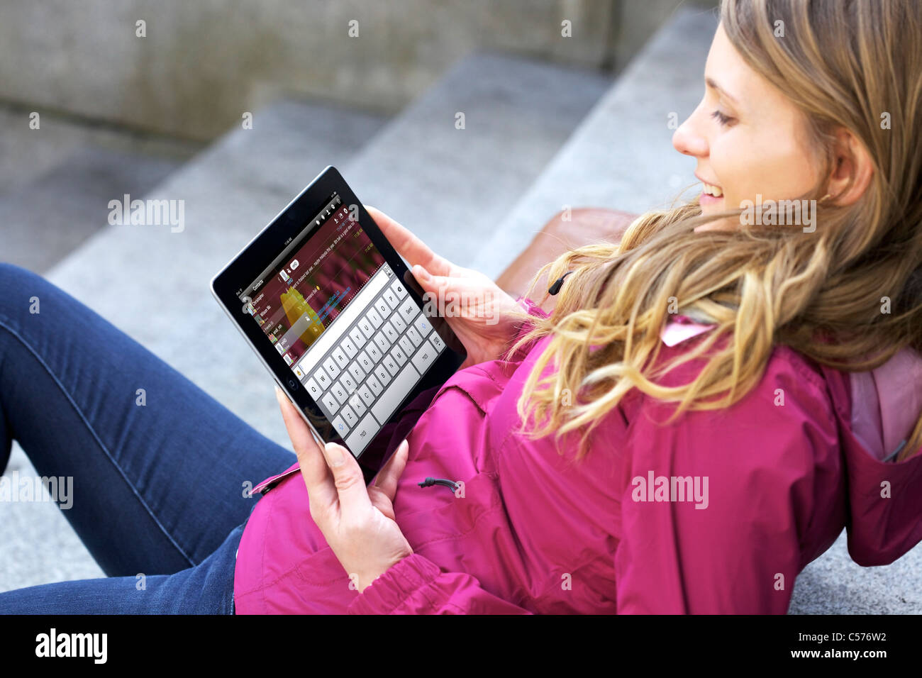View of a Caucasian young woman chatting with IM app (Instant Messaging) app on an iPad 2 through wireless internet - Stock Image