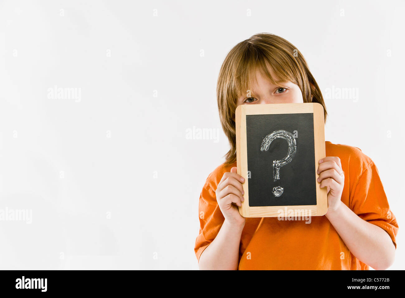 Boy holding question mark on chalkboard - Stock Image