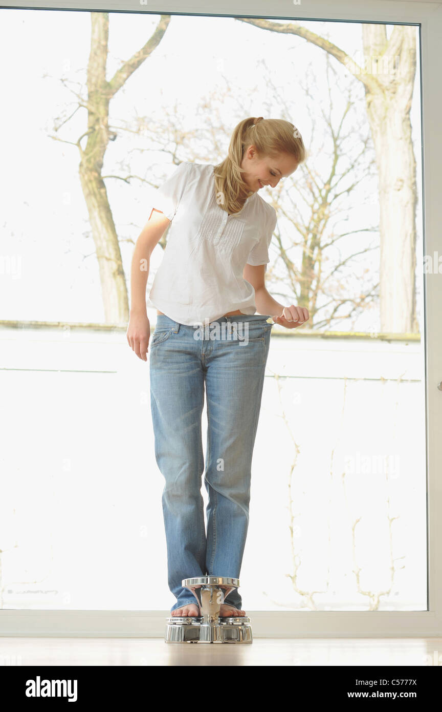 Woman wearing large jeans on scale - Stock Image