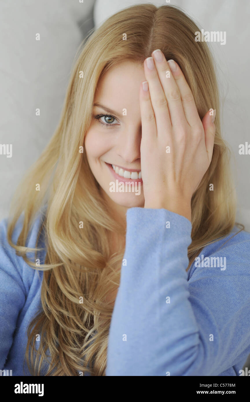 Smiling woman covering one eye - Stock Image