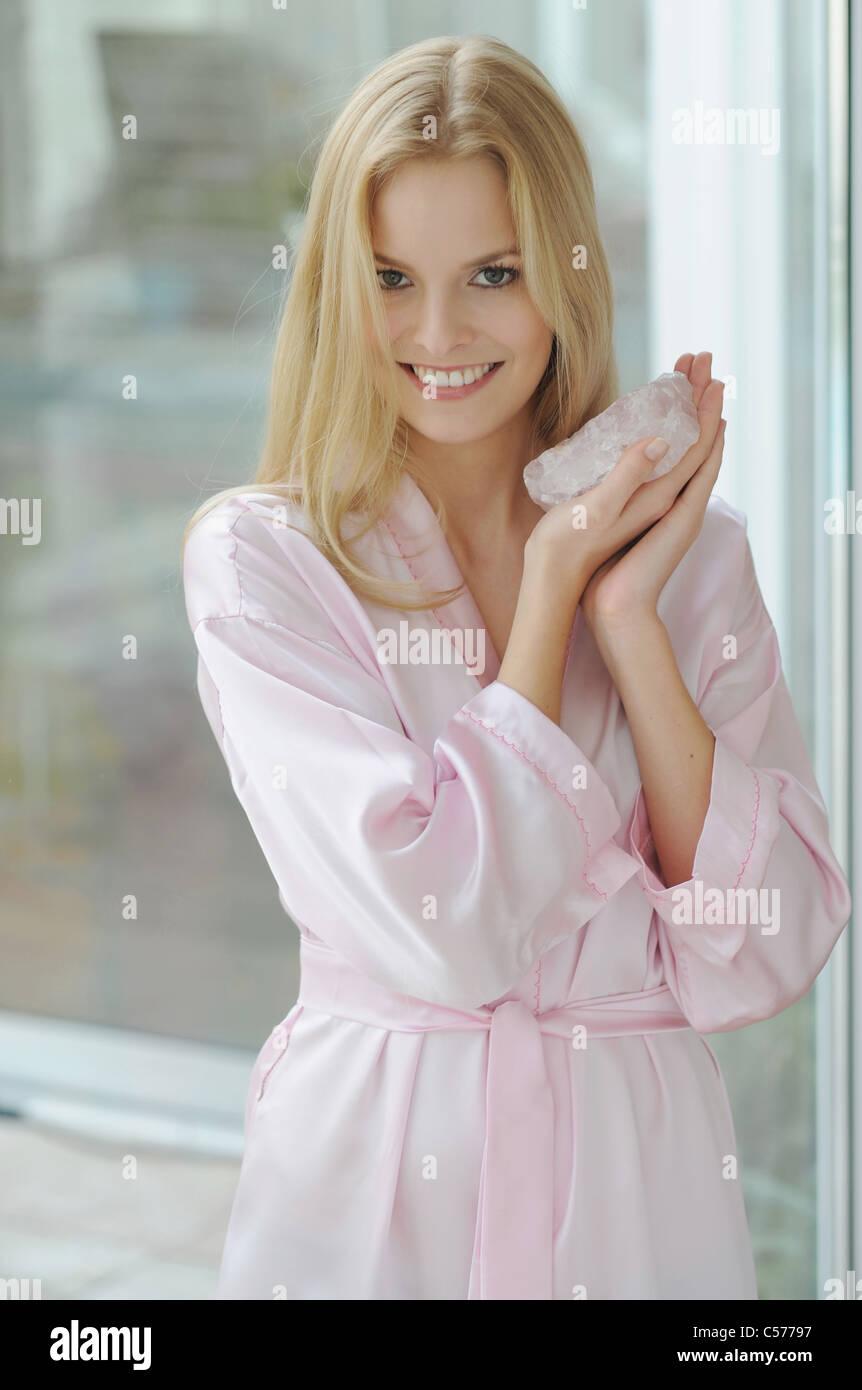 Smiling woman holding rose quartz - Stock Image