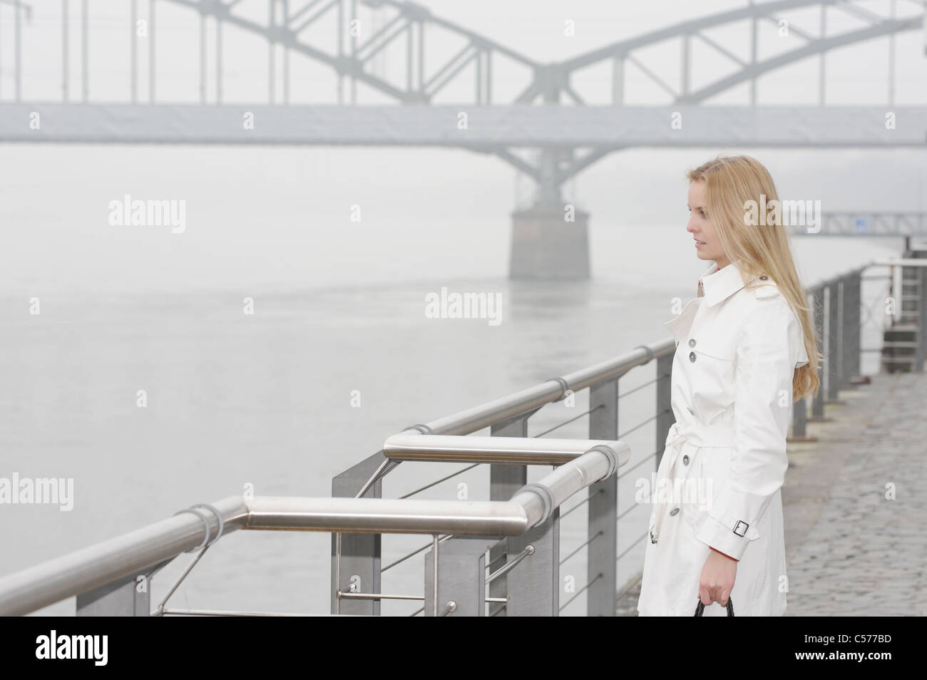 Woman overlooking city river - Stock Image