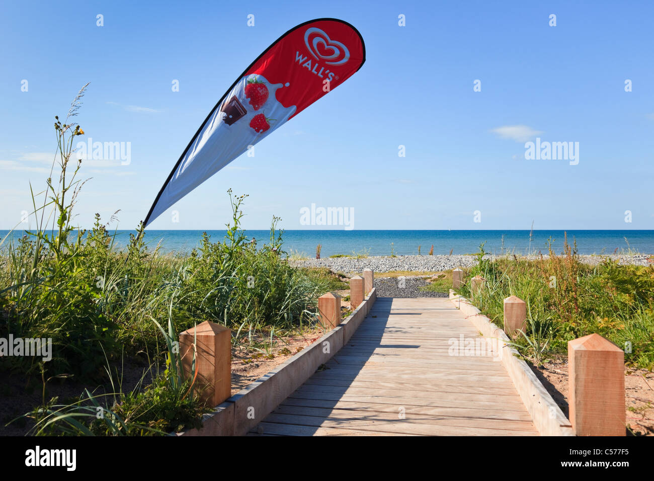 Boardwalk path leading to a beach in Red Wharf Bay with advertisement for Wall's ice creams. Llanddona,Isle - Stock Image