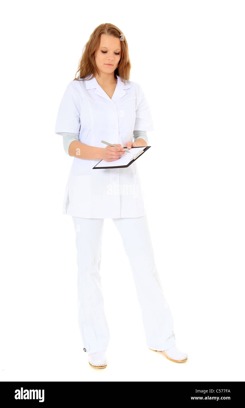 Full length shot of an attractive doctor writing on clipboard. All on white background. - Stock Image