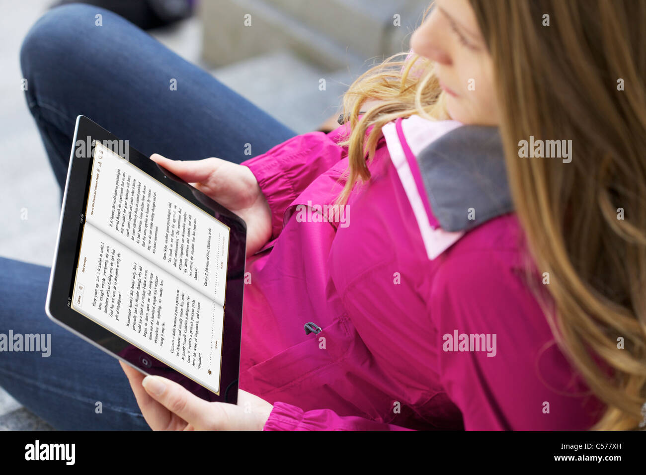 Young caucasian woman reading 'How to Win Friends and Influence People' from iBooks application on an iPad - Stock Image