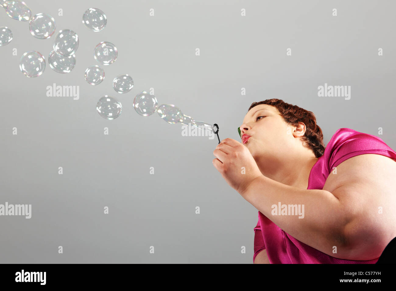 Large woman blowing bubbles Stock Photo