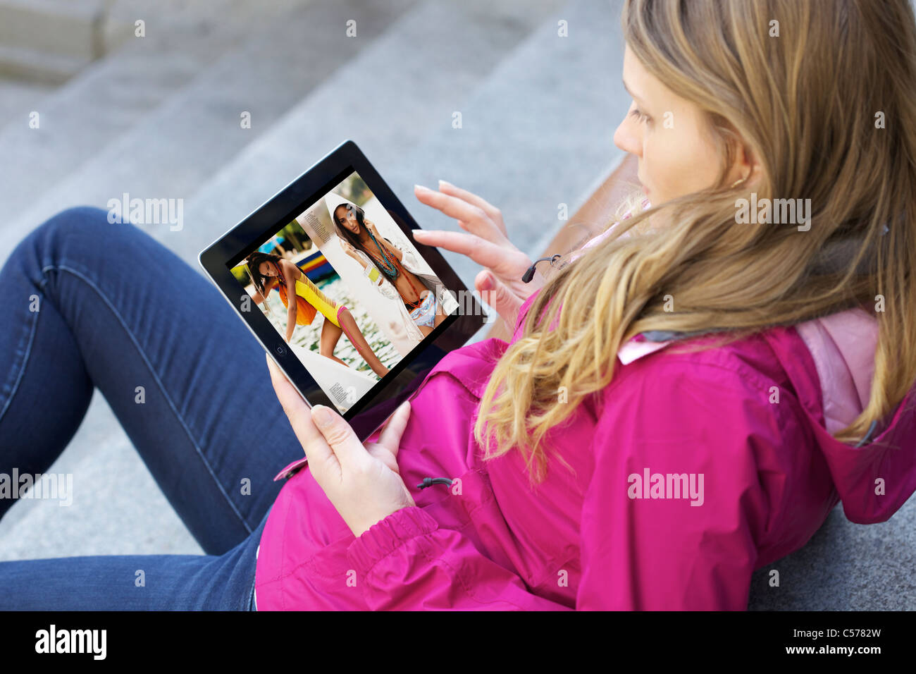 Close up view of young woman reading e-magazine using Zinio online magazine app on an iPad 2 - Stock Image