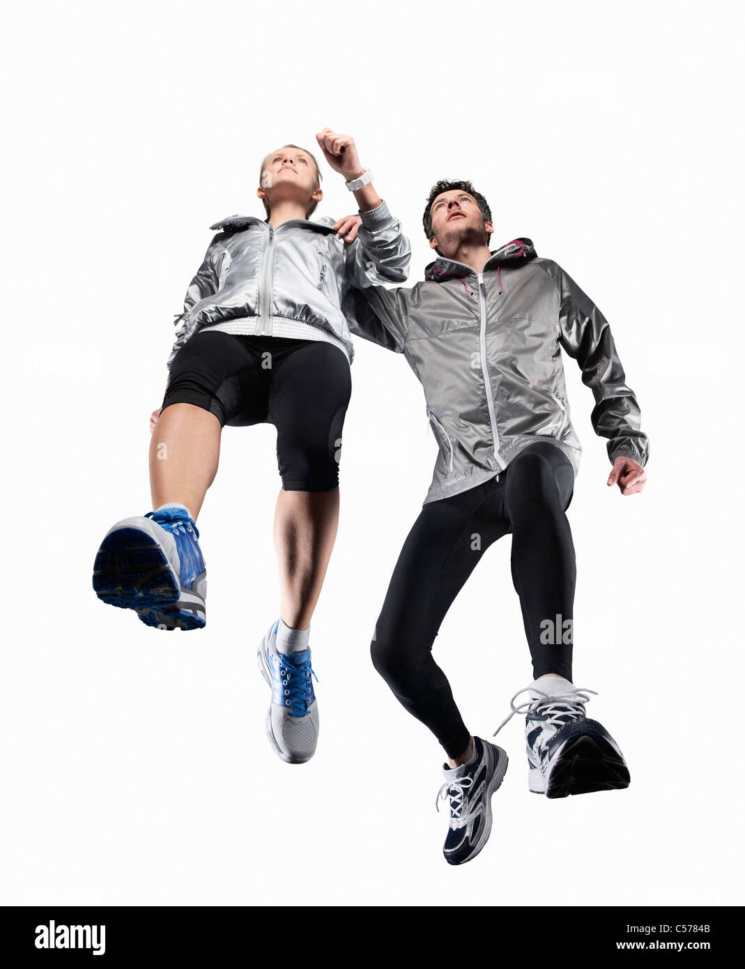 Low angle view of couple jogging - Stock Image
