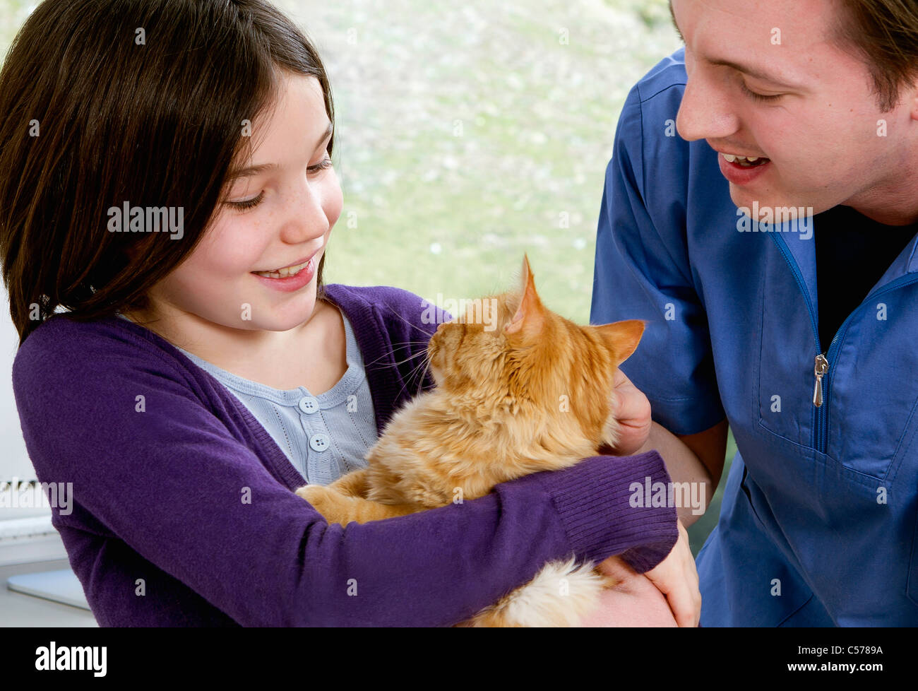 Vet talking to girl with her cat - Stock Image