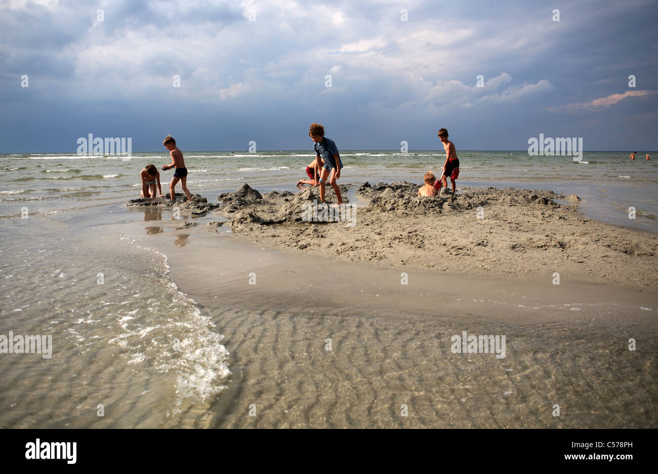 Children playing in the sand on a beach Stock Photo