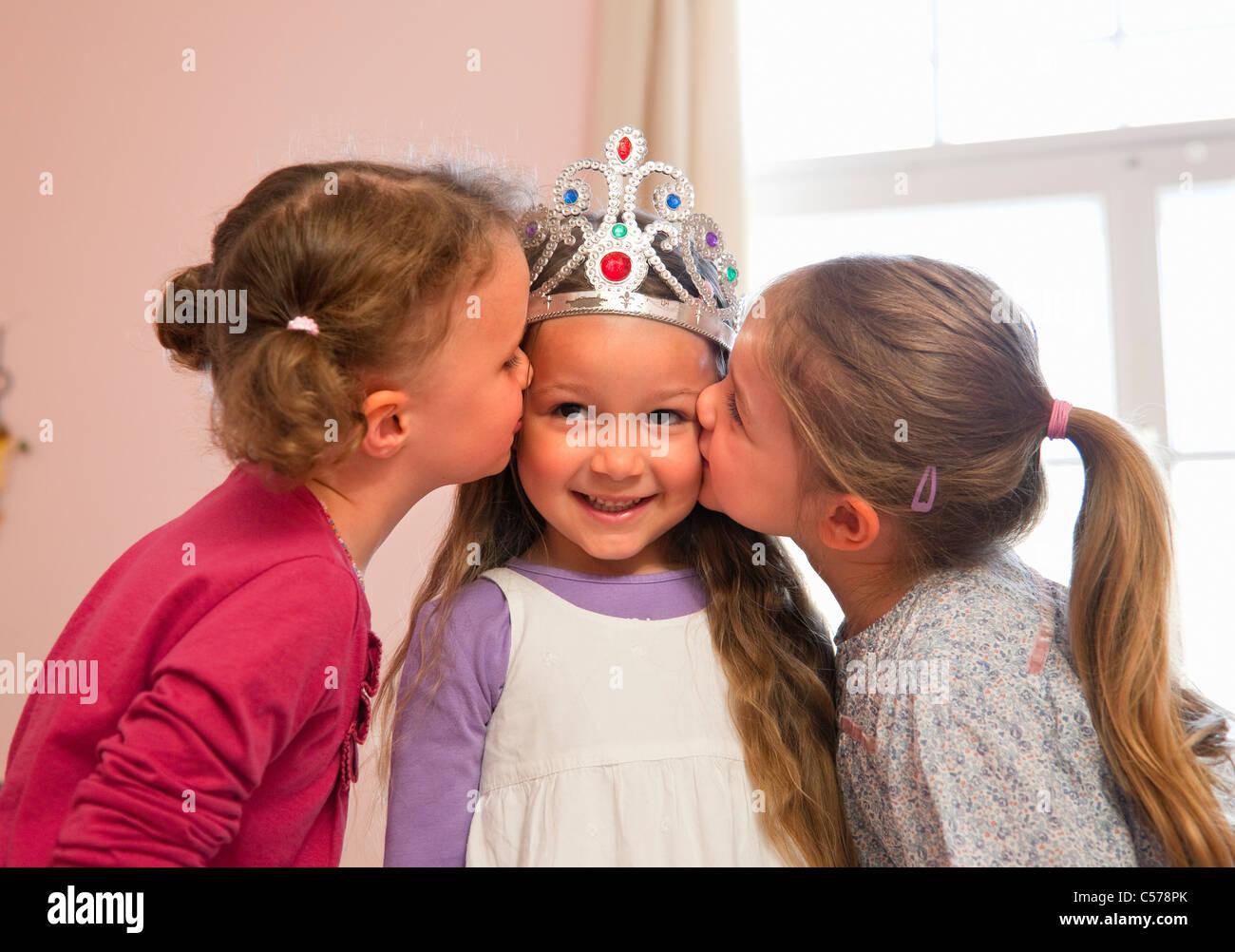 Girls kissing friend's cheeks Stock Photo