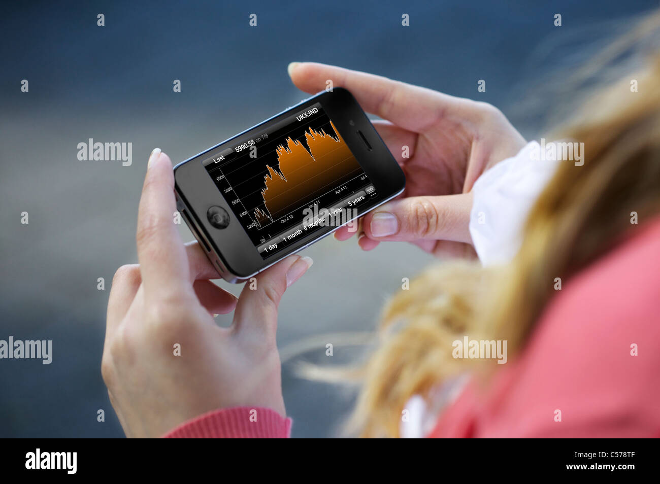 Close up view of a woman checking stock market with Bloomberg finance application on an iphone 4 - Stock Image