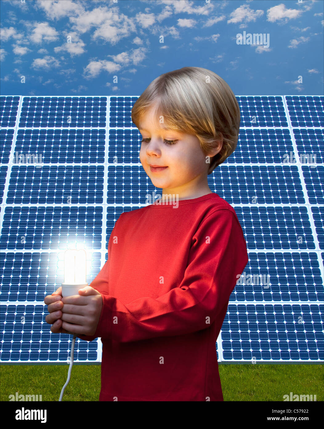 Boy with light bulb by solar panel - Stock Image