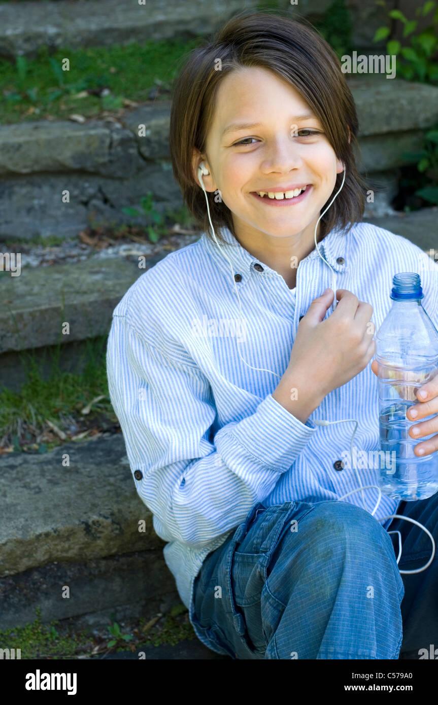 Boy in headphones holding water bottle - Stock Image