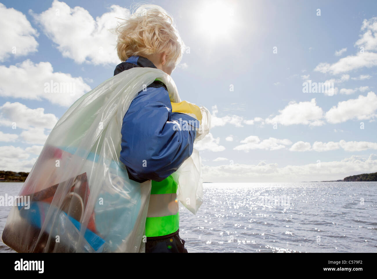 Boy hauling bag of trash on beach - Stock Image