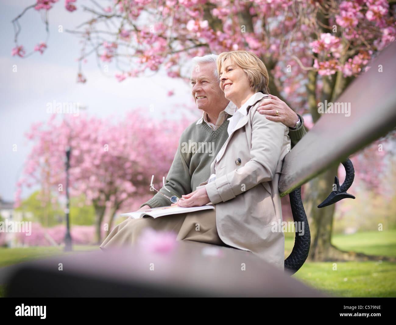 Older couple sitting on park bench - Stock Image