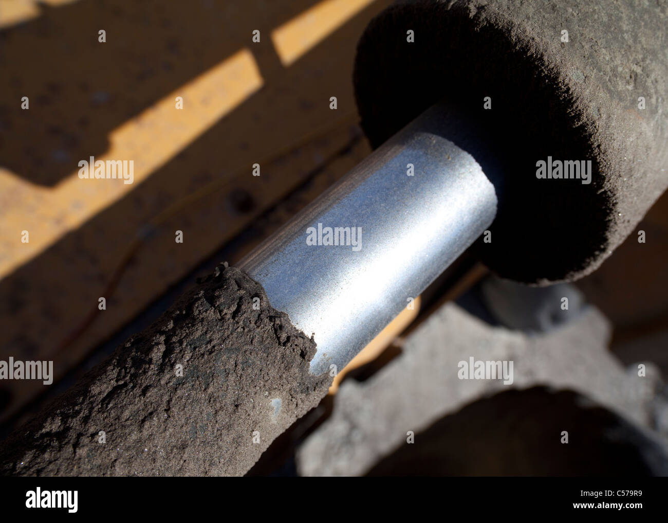 Closeup of greasy and dirty hydraulics cylinder and piston - Stock Image