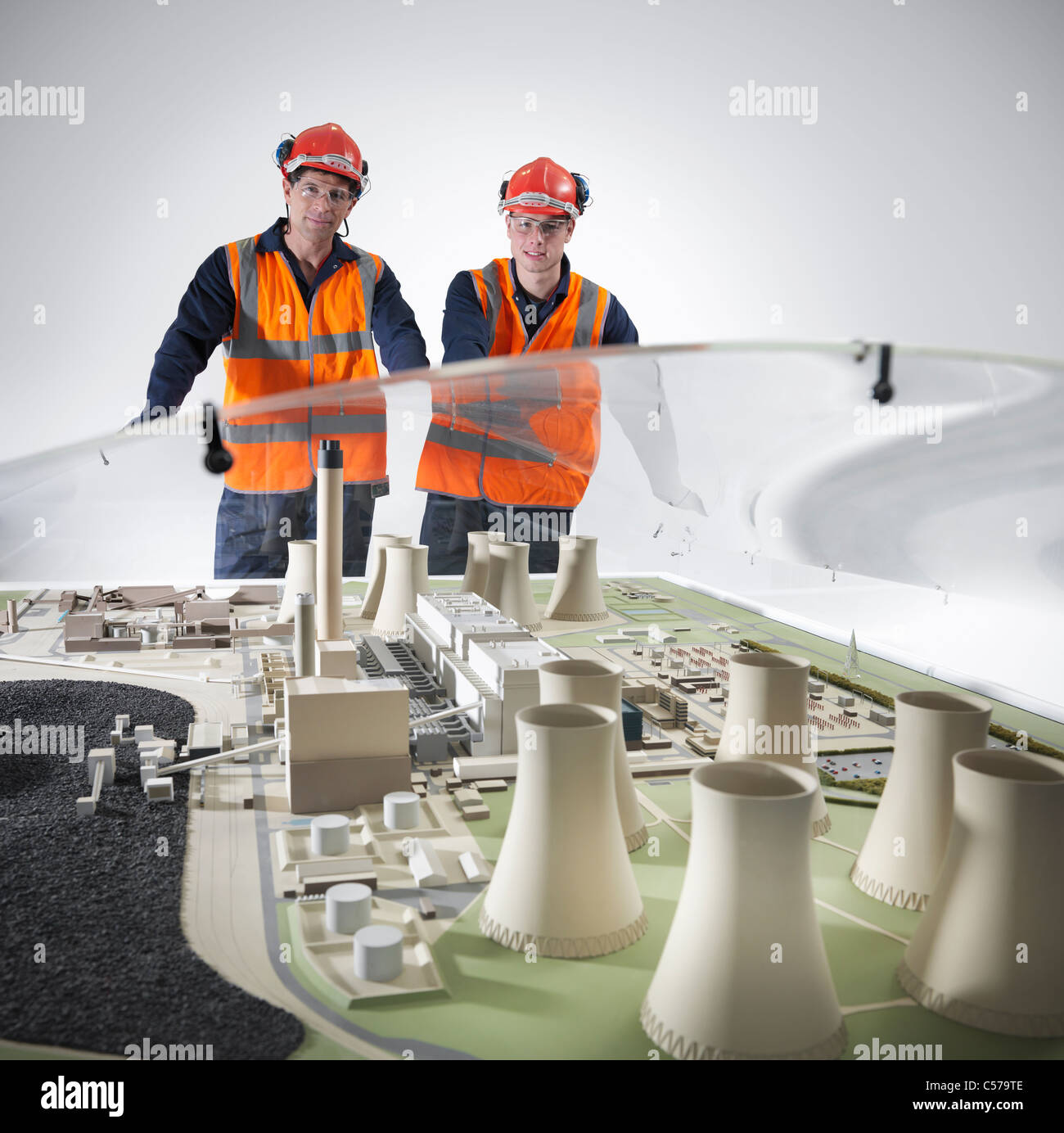 Workers examining model of power station - Stock Image