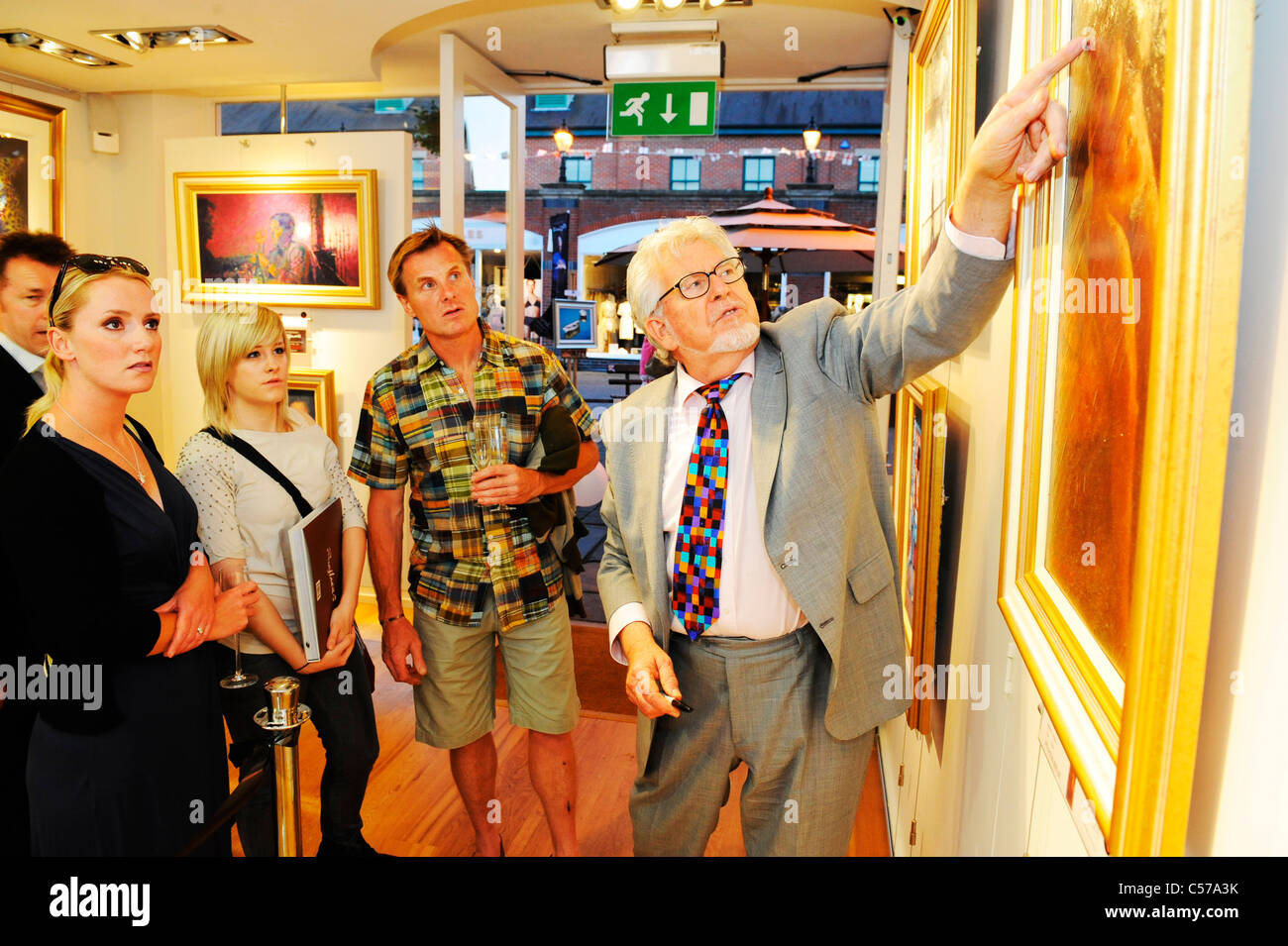rolf harris talks through one of his paintings with members of the public at a art gallery in Windsor - Stock Image