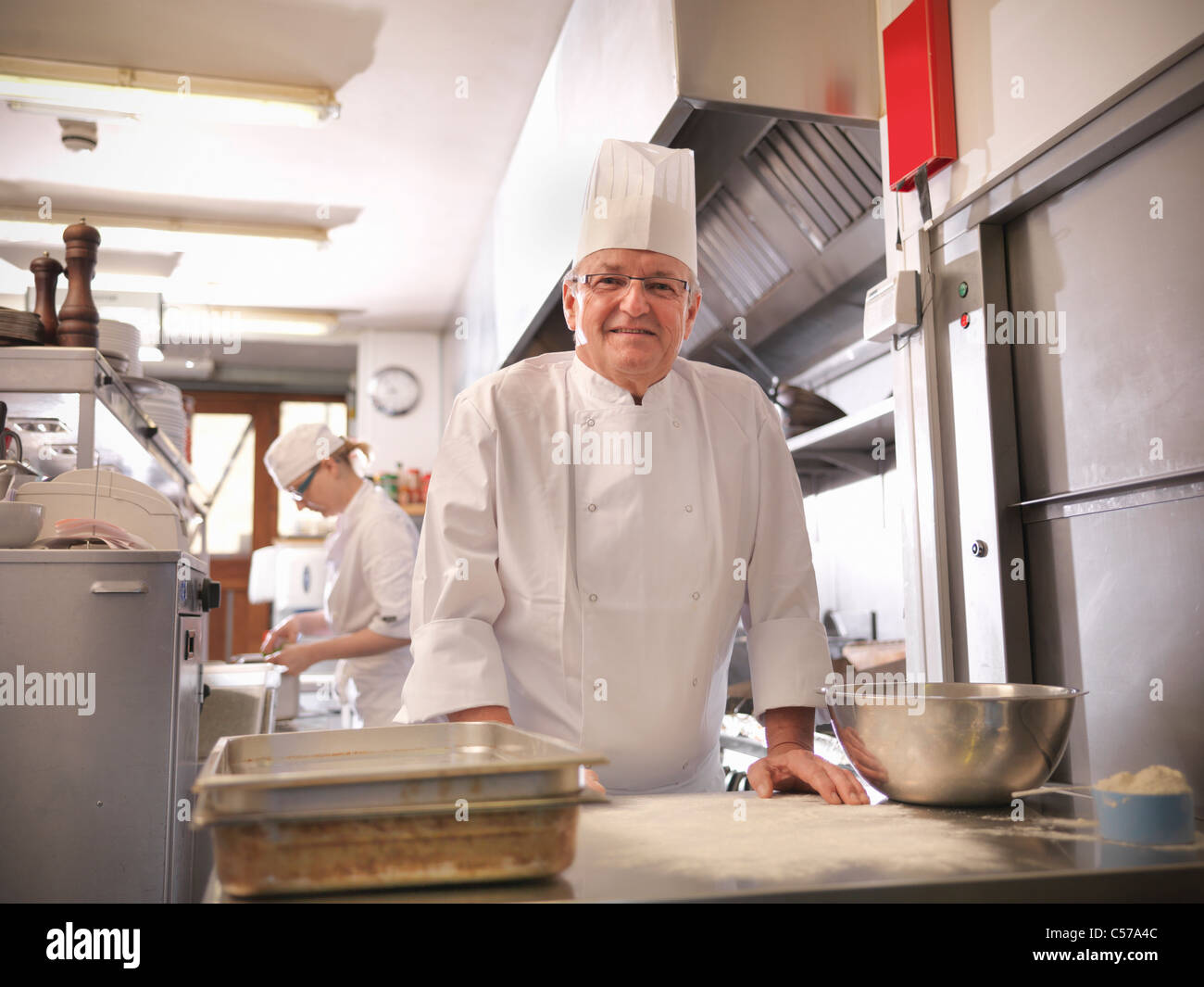 Chef smiling in restaurant kitchen - Stock Image