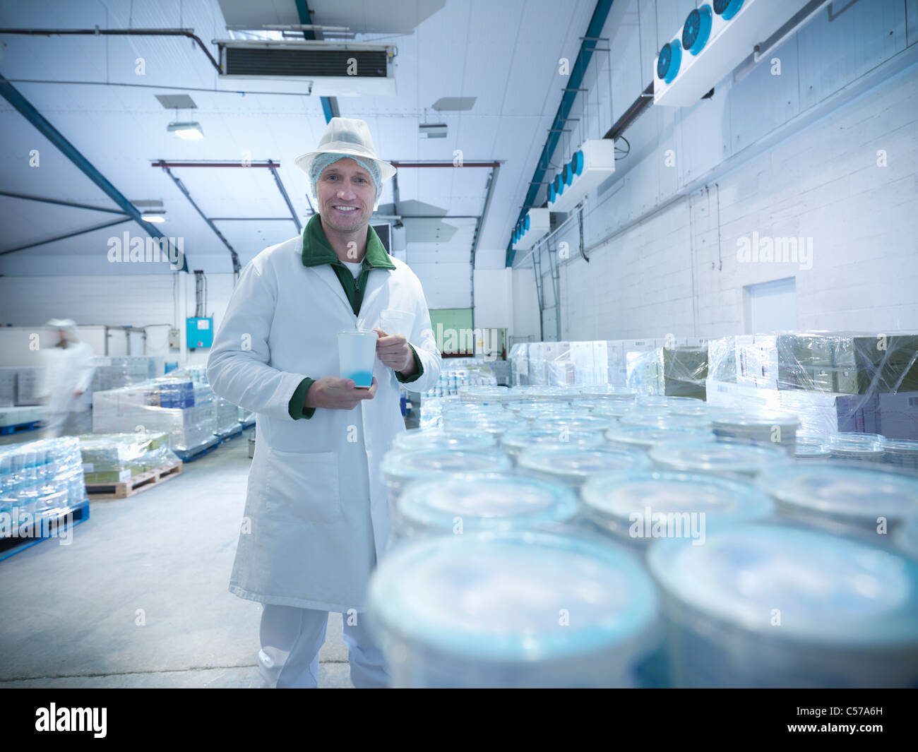 Worker with yogurt in dairy cold store - Stock Image