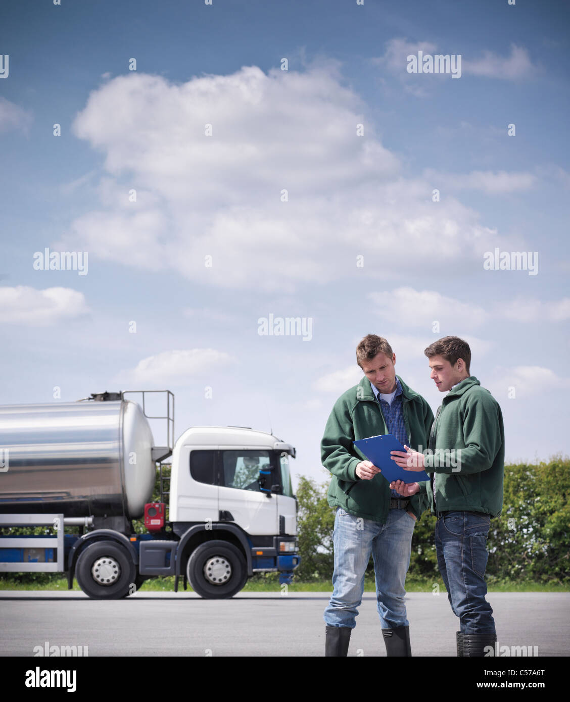 Workers reading clipboard by tanker - Stock Image