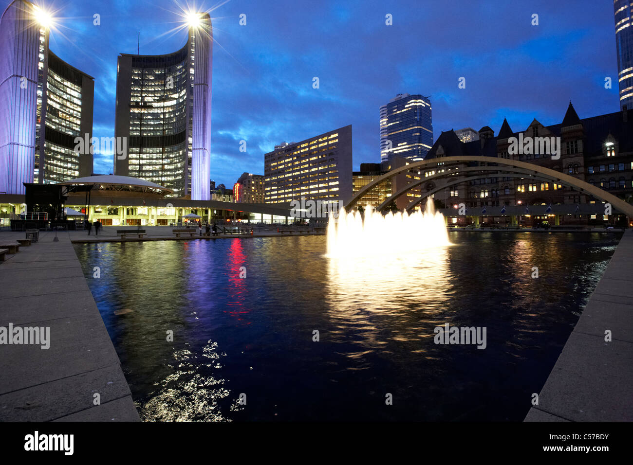 Toronto City Hall building and reflecting pool in nathan phillips square at night - Stock Image