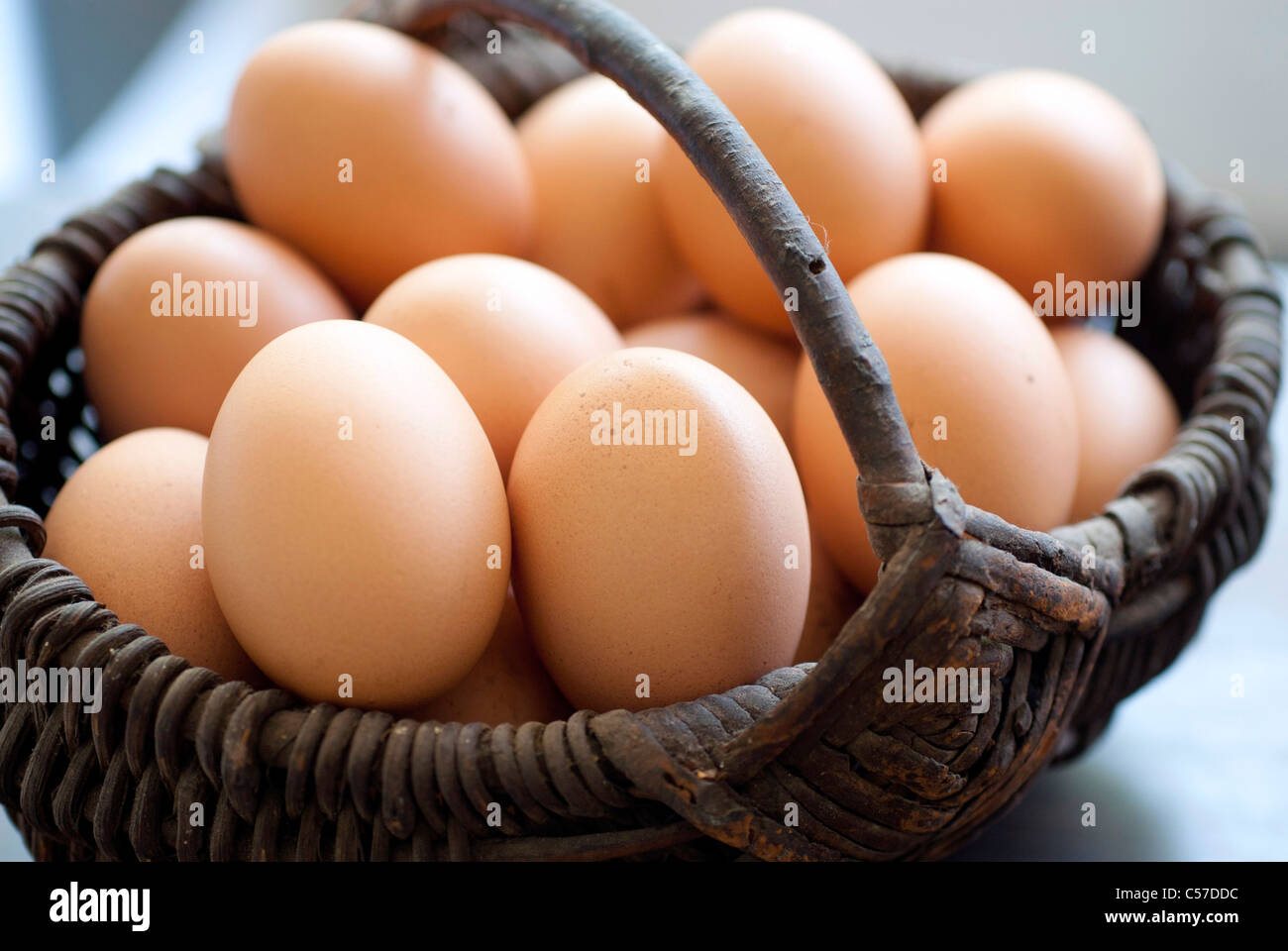 basket full of eggs on a wooden table - Stock Image