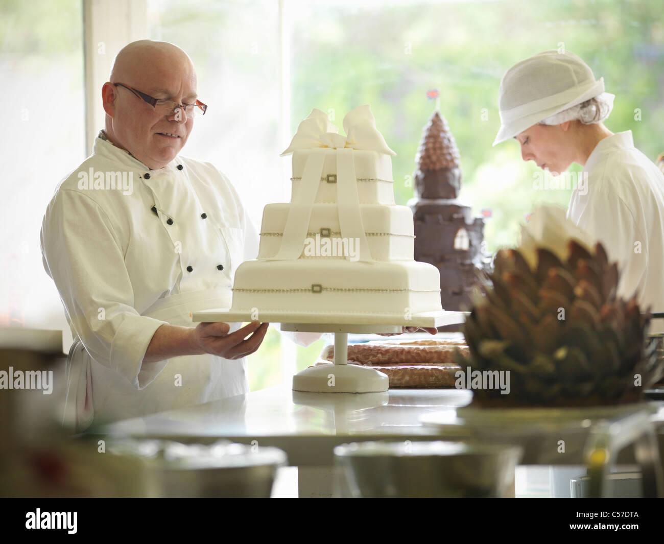 Baker checking decorative wedding cake - Stock Image